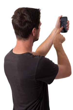 Young White Man In Black T-Shirt Working On His Smartphone photo
