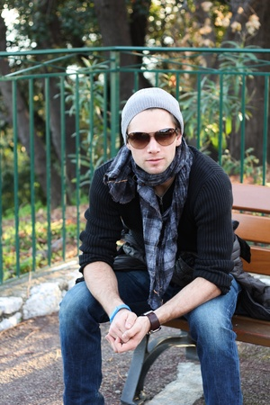 Young stylish man with scarf and beanie sitting on a bench photo