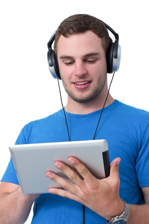 Young man with headphones and blue t-shirt working on a tablet pc Stock Photo - 14929658