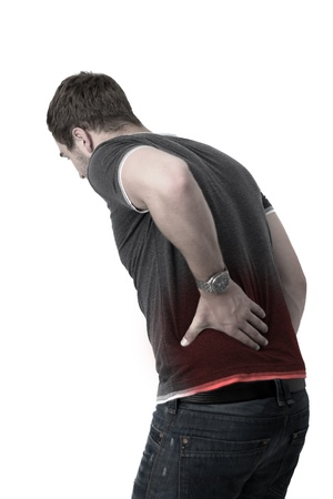 Young man holding his back in pain photo