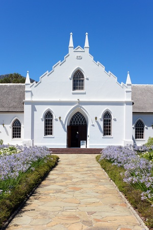 White Church in Franschhoek in front of blue sky with stone pathway photo