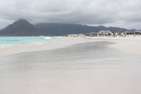 Beach of Kommetjie with an upcoming storm in the background and blue water photo