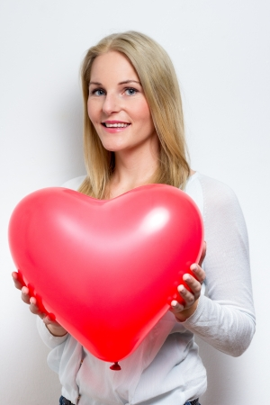 Blond  Smiling Woman Holding a Heart Balloon photo