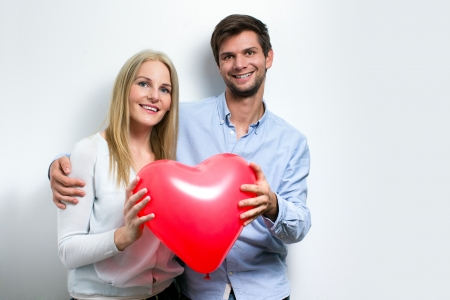 Young couple smiling and holding a red heart photo