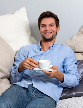 Young brunette man in blue clothing  enjoying a coffeebreak photo