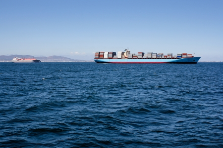 Picture of blue sea with a container ship driving along the horizon photo