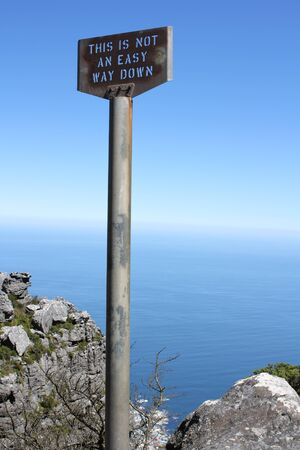 Old signpost on table mountain saying this is not an easy way down photo