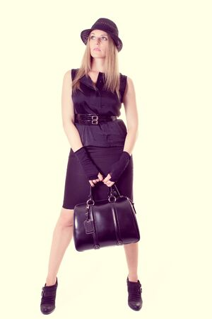 Young blonde Woman in a black outfit holding a bag photo