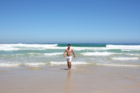 Man running out of indian ocean in south africa photo