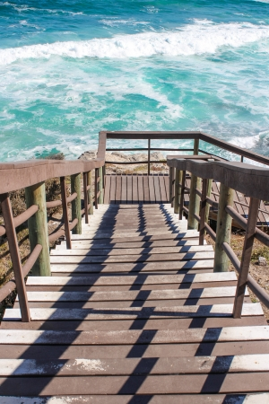 going down: Wooden stairs going down to rough water