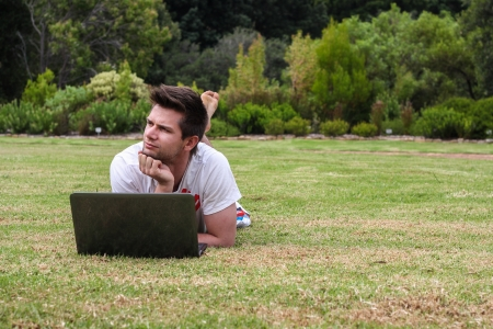 Man working on Notebook outdoors in park Stock Photo