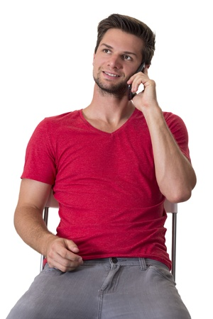 Brunette male student in red t-shirt talking on a cellphone while sitting on a chair Stock Photo - 15435095