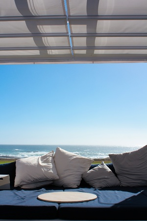 seaview: Beach club couch with ocean in the background Stock Photo