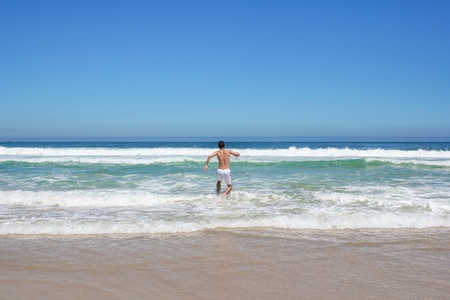 Man running in to indian ocean in south africa photo