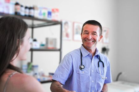 Smiling Male Doctor in his fifties Helping  brunette Woman Stock Photo - 15635346