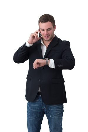 Young Man in jacket talking on the phone and looking at watch photo