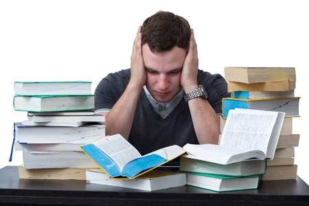 stressed out: Young Student overwhelmed with studying with piles of books in front of him Stock Photo