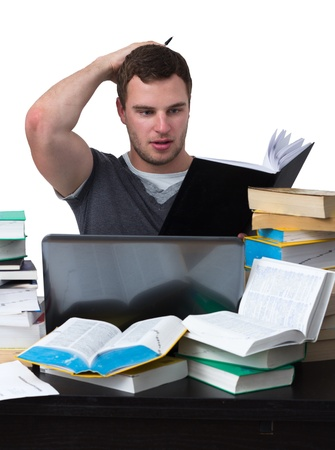 Young Student overwhelmed with studying with piles of books in front of him Stock Photo - 15867752