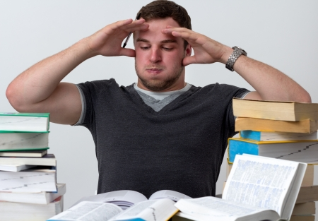 Young Student overwhelmed with studying with piles of books in front of him Stock Photo