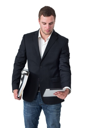 Businessman in front of isolated background looking at tablet pc and holding ring binder Stock Photo - 16336987