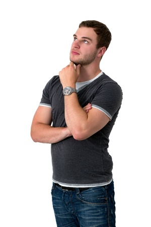 Young man in jeans and grey shirt thinking in front of white isolated background Stock Photo - 16336989