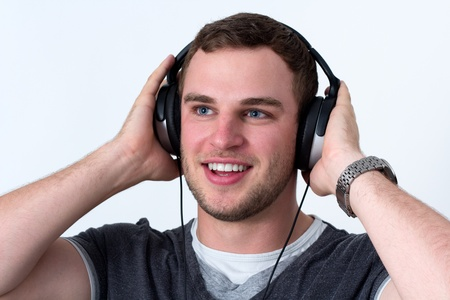 Close up of face of young man in grey t-shirt listening to music with earphones Stock Photo - 16375064