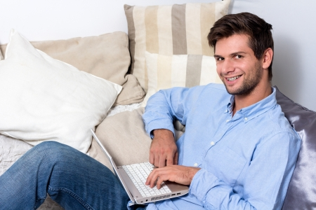 man using computer: Young brunette man in blue shirt using laptop on couch
