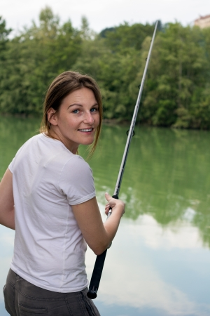Brunette Woman Fishing at a lake with green water Stock Photo