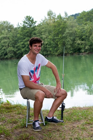 Brunette Man Fishing at a lake with green water photo