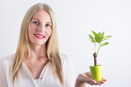 Young woman with small tree smiling happily Stock Photo - 16883859