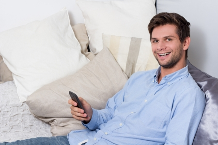 Young brunette man in blue shirt using cellphone on couch photo