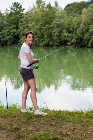 Brunette Woman Fishing at a lake with green water Stock Photo - 16883864