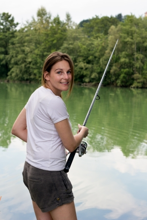 Brunette Woman Fishing at a lake with green water Stock Photo - 16883863