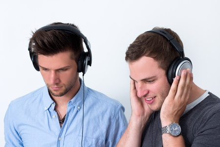 Two friends with headphone listening to music in front of a white background photo