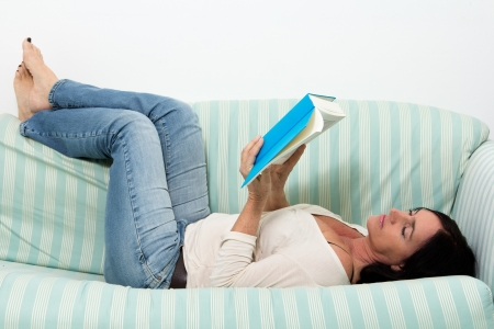 dark haired woman: Dark haired woman lying on couch and reading a blue book Stock Photo