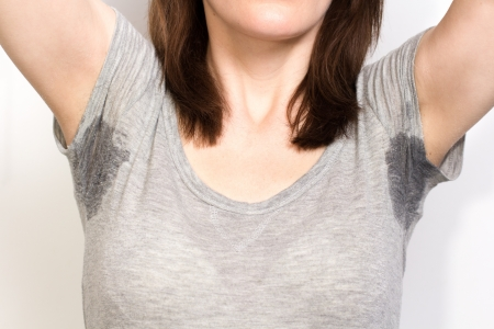 Woman sweating very badly under armpit and holding nose photo