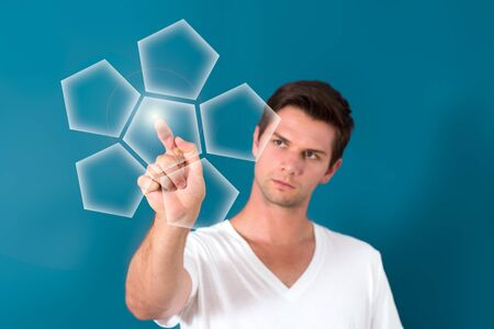 Brunette man Pressing Virtual Button with a blue background photo