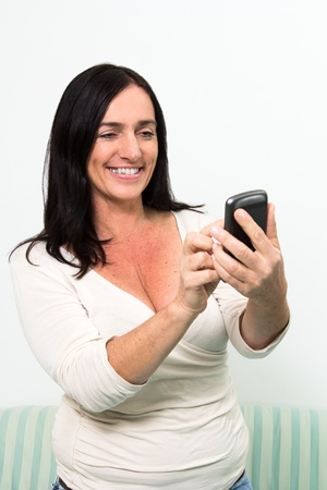 dark haired woman: Dark haired woman using touchscreen of a Smartphone