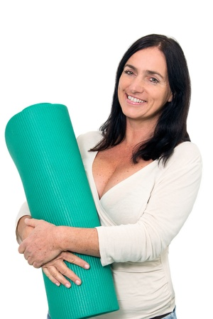 dark haired woman: Dark haired Woman with an exercise matt in front of isolated background Stock Photo