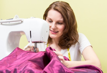 brunett: Brunette european woman sewing diy at home in front of yoellow background Stock Photo