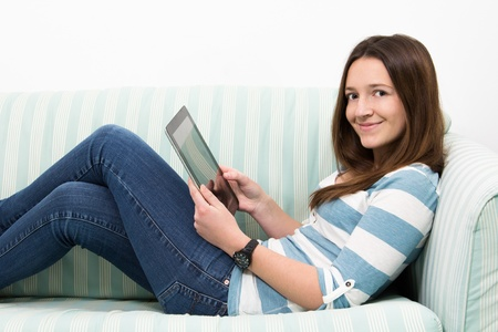 Brunette Teenage Girl Working On A Tablet PC whole lying on a couch photo