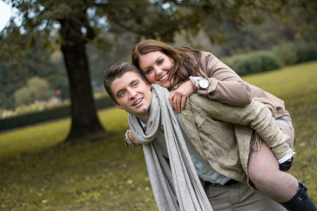 Young caucasian couple in love piggybacking at a park in austria in autumn photo