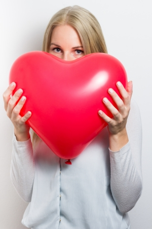 Blonde woman hiding her face behind a red heart for valentin´s day photo