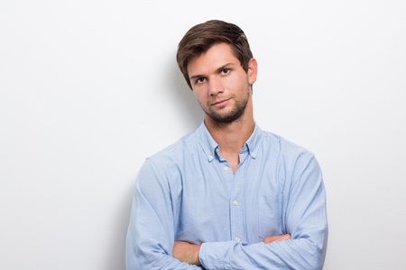 likeable: Brunette man with one arm folded wearing a blue shirt Stock Photo
