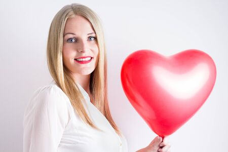 realtionship: Blond woman with long hear wearing a white blouse and holding a red heart balloon