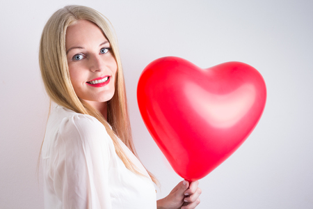 realtionship: Blonde woman with long hear wearing a white blouse and holding a red heart balloon