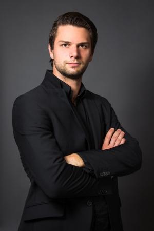 traje: Hombre en juego de Negro en frente de un fondo gris que parece seria