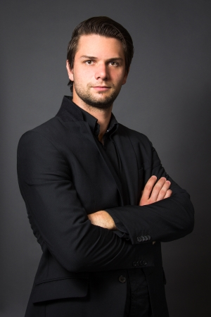 Man in zwart pak in voor een grijze achtergrond zoekt ernstig Stockfoto
