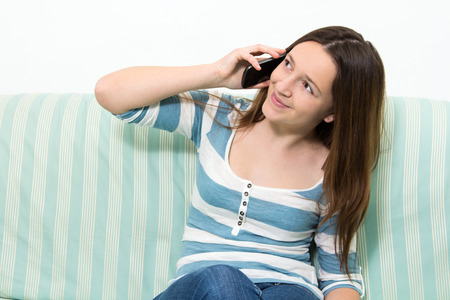 phone conversation: Young brunette girl with a blue and white striped top talking on the phone