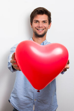 Brunette man wearing a blue shirt and holding a red heart balloon photo